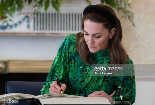 Catherine, Duchess of Cambridge signs a book as she arrives for a meeting with the President of Ireland at Áras an Uachtaráin on March 03, 2020 in...