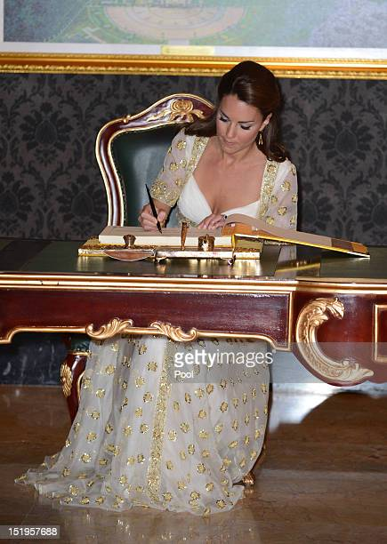 Catherine Duchess of Cambridge signs the visitors' book during an official dinner hosted by Malaysia's Head of State Sultan Abdul Halim Mu'adzam Shah...