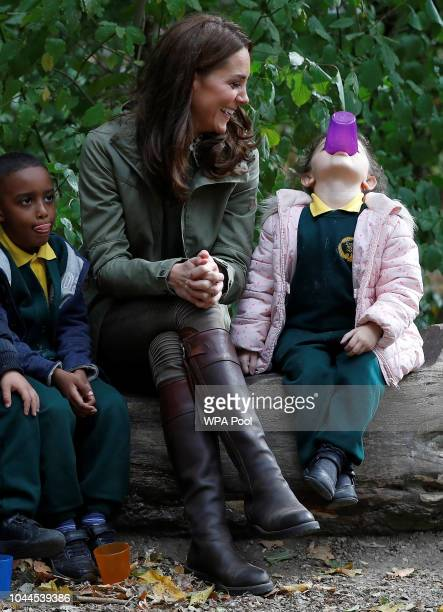 Catherine Duchess of Cambridge sits on a log with children during a visit to Sayers Croft Forest School and Wildlife Garden on October 2 2018 in...