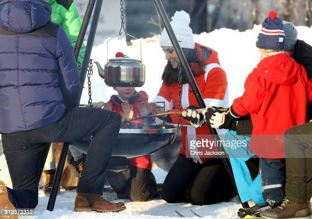 Catherine Duchess of Cambridge smiles and warms her hands as she attends an event organised by the Norwegian Ski Federation with Prince William Duke...