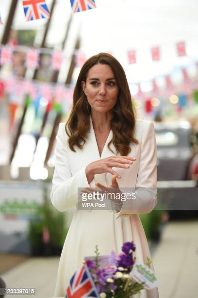 Catherine, Duchess of Cambridge, speaks as she attends an event with Queen Elizabeth II in celebration of The Big Lunch initiative at The Eden...