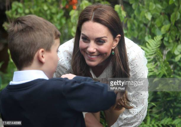 Catherine Duchess of Cambridge speaks children during a visit to her garden at the RHS Chelsea Flower Show at the Royal Hospital Chelsea on May 20...