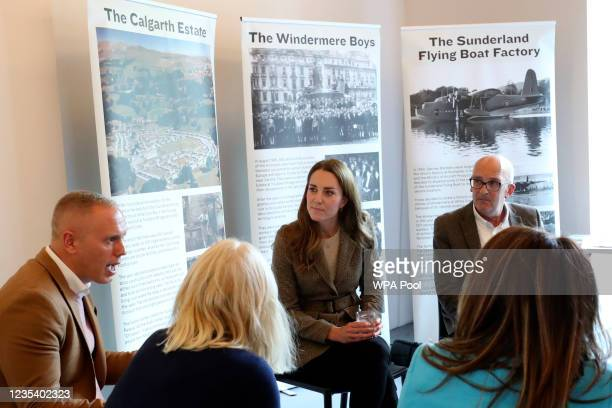Catherine, Duchess of Cambridge speaks to family members of the 'Windermere Children' and television personality Robert Rinder, left, during a visit...