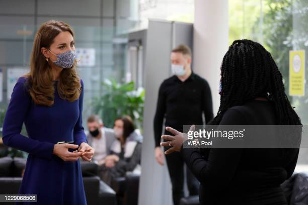 Catherine Duchess of Cambridge speaks to Obiele Laryea as she meets families during a visit to the Institute of Reproductive and Development Biology...