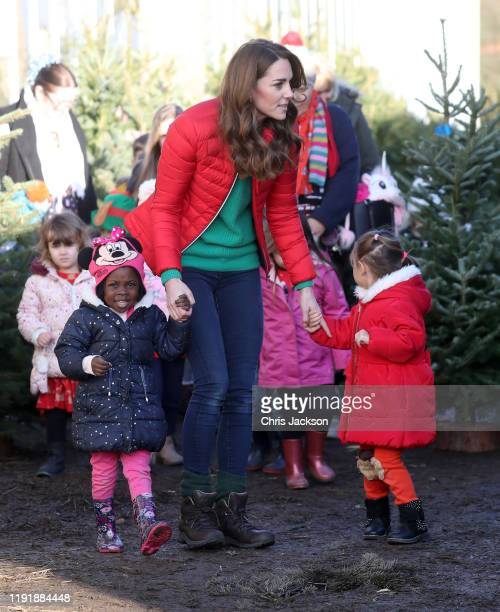 Catherine, Duchess of Cambridge speaks to young children as she helps pick Christmas trees for preschool during a visit to the charity Family Action...