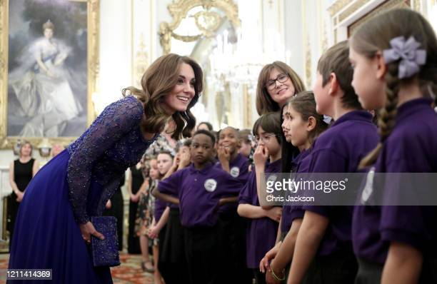 Catherine Duchess of Cambridge speaks with a school choir as she hosts a Gala Dinner in celebration of the 25th anniversary of Place2Be at Buckingham...
