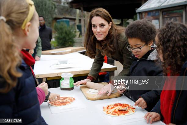Catherine, Duchess of Cambridge speaks with children and helps makes pizza as she visits Islington Community Garden on January 15, 2019 in London,...