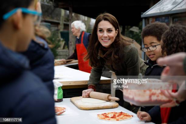 Catherine Duchess of Cambridge speaks with children and helps makes pizza as she visits Islington Community Garden on January 15 2019 in London...