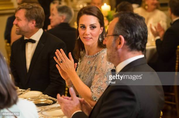 Catherine Duchess of Cambridge speaks with French actor Jean Reno during a dinner hosted by Her Majesty's Ambassador to France Edward Llewellyn at...