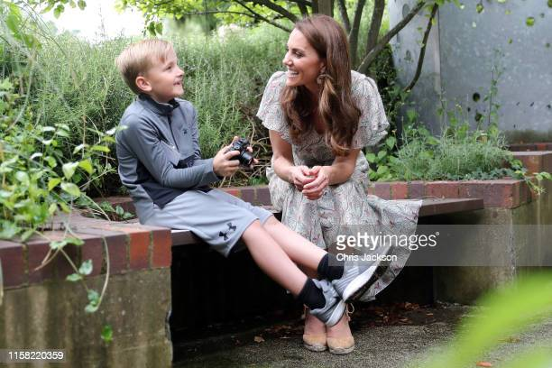 Catherine Duchess of Cambridge speaks with Josh Evans at photography workshop for Action for Children run by the Royal Photographic Society at Warren...