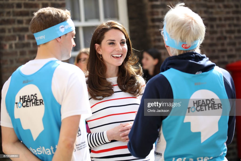 Catherine, Duchess of Cambridge speaks with runners after they put a Heads Together headband onto the Kensington Palace post-box in support of the Royal Mail wrapping 70 post-boxes that line the 2017 Virgin Money London Marathon route ahead of a reception for Team Heads Together, at Kensington Palace on April 19, 2017 in London, England. Heads Together is spearheaded by the Duke and Duchess of Cambridge and Prince Harry, in partnership with eight leading mental health charities that are tackling stigma, raising awareness, and providing vital help for people with mental health problems.