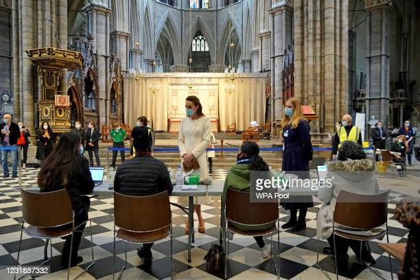 Catherine, Duchess of Cambridge speaks with staff during a visit to the Covid-19 vaccination centre at Westminster Abbey on March 23, 2021 in London,...