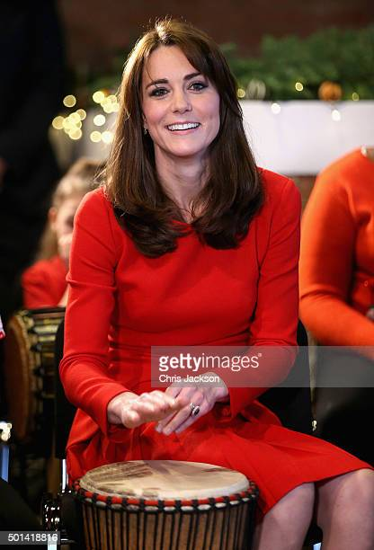 Catherine Duchess of Cambridge takes part in some drumming 'music therapy' as she attends the Anna Freud Centre Family School Christmas Party at Anna...