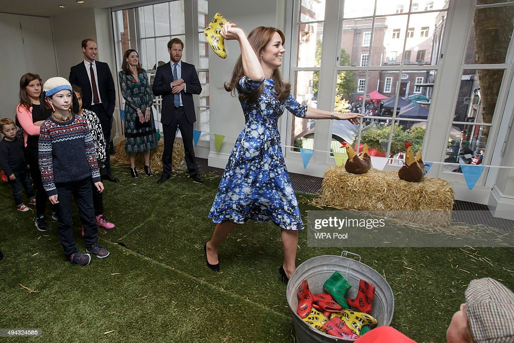 Catherine, Duchess of Cambridge takes part in welly wanging, watched by the Prince William, Duke of Cambridge, back left, and Prince Harry, centre, with children and representatives from charities and Aardman Animations, during a meeting of the Charities Forum at BAFTA on October 26, 2015 in London, United Kingdom.