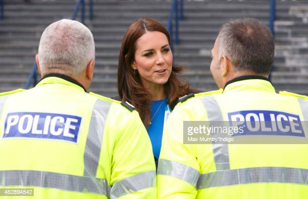 Catherine Duchess of Cambridge talk with Police Motorcycle Outriders as she leaves Hampden Park after watching the athletics during the 20th...