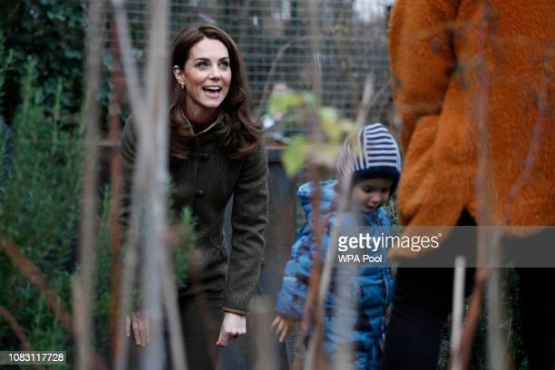 Catherine Duchess of Cambridge talks to a mother and child as she visits Islington Community Garden on January 15 2019 in London England