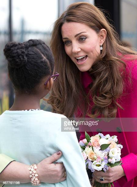 Catherine Duchess of Cambridge talks to a young girl who presented her with a poesy of flowers as she leaves the Stephen Lawrence Centre in Deptford...