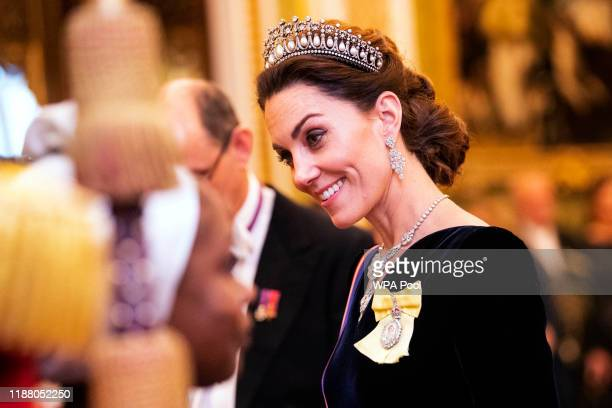 Catherine, Duchess of Cambridge talks to guests at an evening reception for members of the Diplomatic Corps at Buckingham Palace on December 11, 2019...