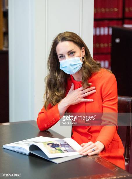 Catherine, Duchess of Cambridge talks to 'Hold Still' entrants during a visit to the archive in the National Portrait Gallery in central London to...