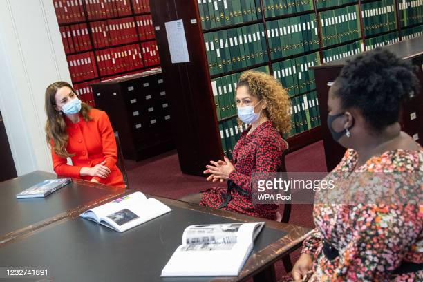 Catherine, Duchess of Cambridge talks to 'Hold Still' entrants Naz Maleknia and Claudia Burton during a visit to the archive in the National Portrait...