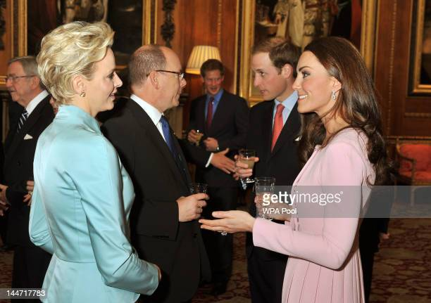 Catherine Duchess of Cambridge talks to Princess Charlene of Monaco as Prince Albert II of Monaco and Prince William Duke of Cambridge talk during a...