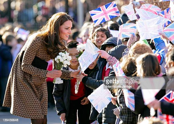 Catherine Duchess of Cambridge talks with flag waving school children as she arrives for a visit to The Art Room's classroom at Rose Hill Primary...