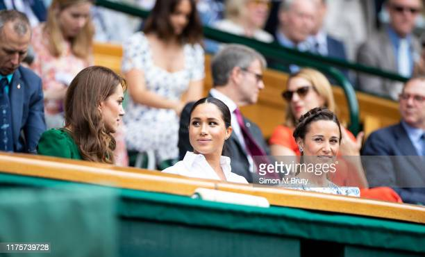 Catherine, Duchess of Cambridge talks with Meghan, Duchess of Sussex and Pippa Middleton in the royal box before the start of the Women's Singles...