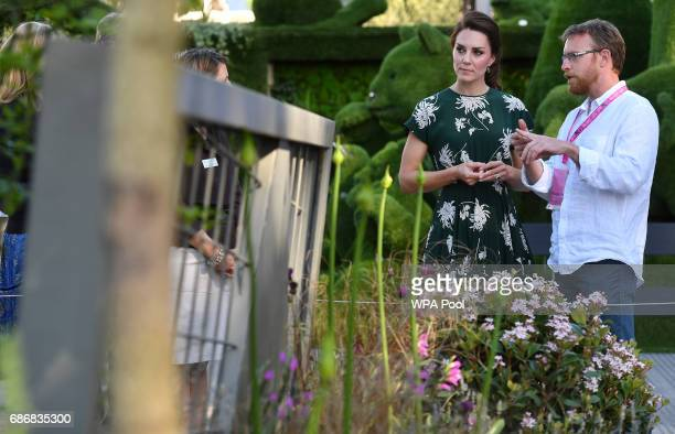 Catherine Duchess of Cambridge talks with Northern Irish designer Ian Price as she views his garden 'Mind Trap' at the RHS Chelsea Flower Show press...