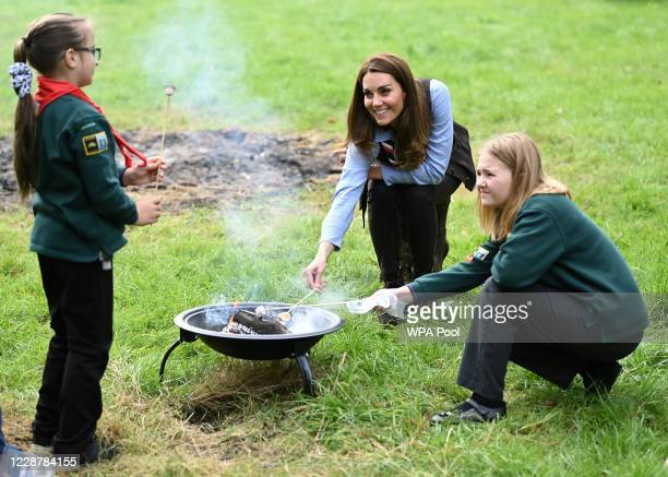 Catherine, Duchess of Cambridge toasts marshmallows during her visit to a Scout Group in Northolt, northwest London where she joined Cub and Beaver...