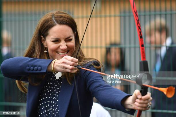 Catherine, Duchess of Cambridge tries archery during a visit to The Way Youth Zone on May 13, 2021 in Wolverhampton, England.