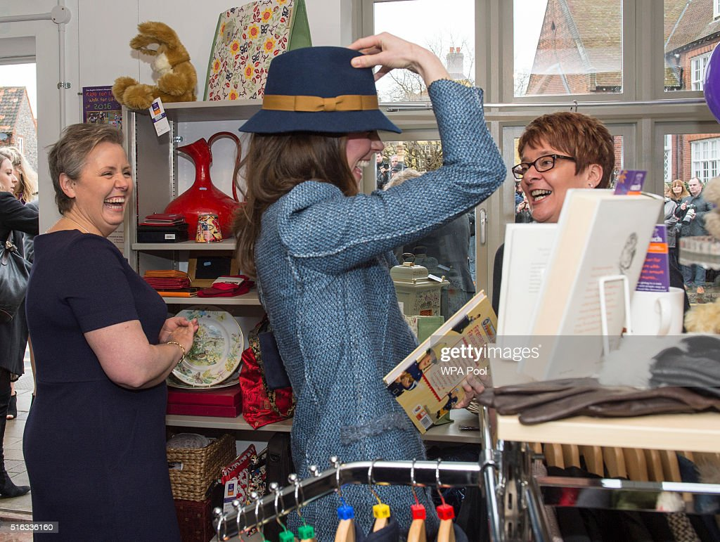 Catherine, Duchess of Cambridge tries on a Boden hat, priced at £15, as she takes a tour of the new EACH charity shop that she officially opened earlier today on March 18, 2016 in Holt, United Kingdom.