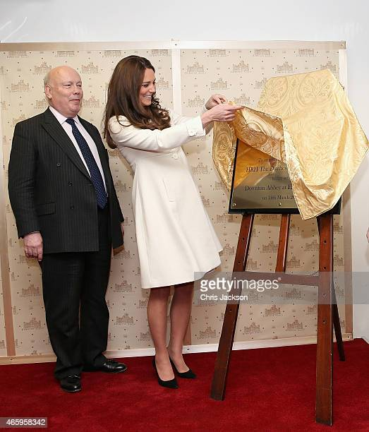 Catherine Duchess of Cambridge unveils a plaque as Lord Julian Fellowes looks on during an official visit to the set of Downton Abbey at Ealing...