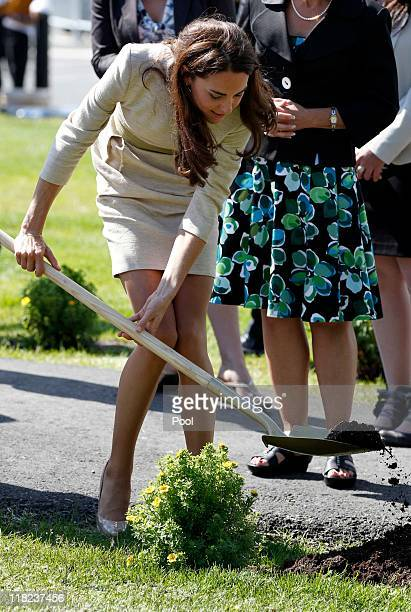 Catherine Duchess of Cambridge uses a shovel as she plants a shrub during her visit with her husband Prince William Duke of Cambridge to the Somba...