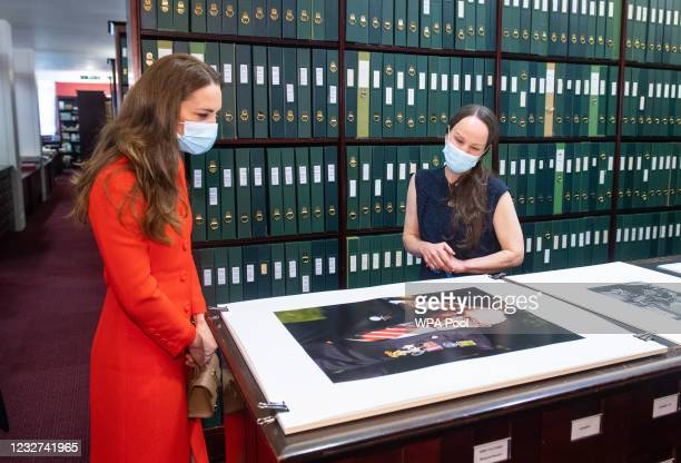 Catherine, Duchess of Cambridge views a photo of Captain Tom Moore alongside Curator Magda Keaney during a visit to the archive in the National...