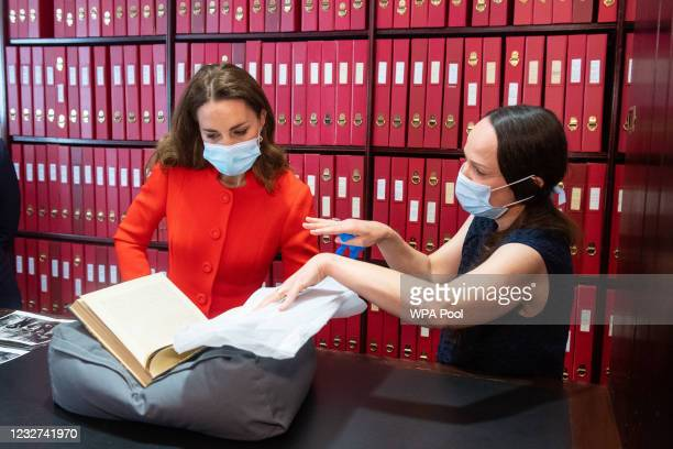 Catherine, Duchess of Cambridge views archives alongside Curator Magda Keaney during a visit to the archive in the National Portrait Gallery in...