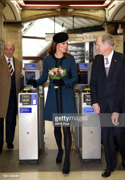 Catherine Duchess of Cambridge walks through a ticket barrier as she makes an official visit to Baker Street Underground Station to mark 150th...