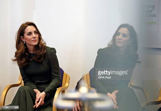 Catherine Duchess of Cambridge watches a video presentation while reflected in a watches a video presentation while reflected in a glass door during...