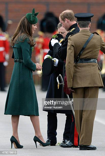 Catherine Duchess of Cambridge watches Prince William Duke of Cambridge put a shamrock in his cap during the St Patrick's Day Parade at Mons Barracks...