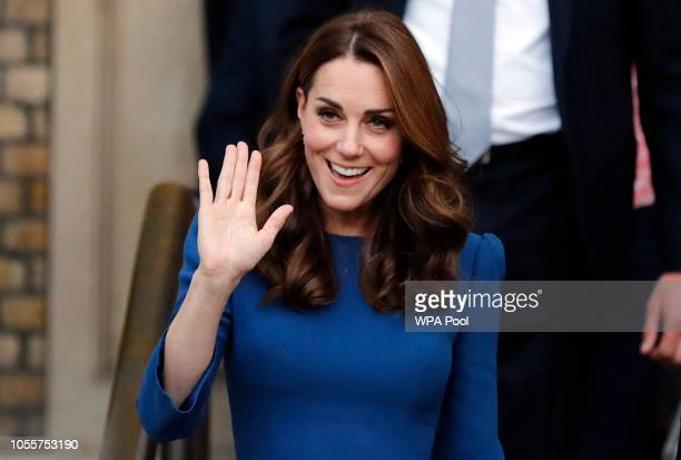 Catherine Duchess of Cambridge waves as she arrives to tour the First World War Galleries with historians and curators before viewing letters...