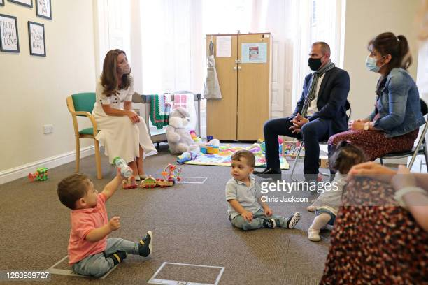 Catherine Duchess of Cambridge wearing a face mask talks to the family of Ali Wartty Sahara Hamawandy and their triplets San Shan and Laveen who got...