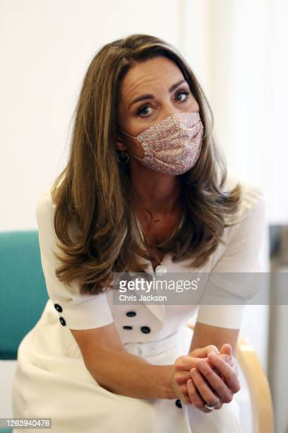 Catherine, Duchess of Cambridge, wearing a face mask, talks to the family of Ali Wartty, Sahara Hamawandy and their triplets San, Shan and Laveen,...
