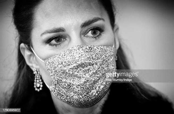 Catherine, Duchess of Cambridge wears a floral print face mask as she attends an event to thank local volunteers and key workers from organisations...