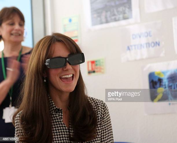 Catherine, Duchess of Cambridge wears a pair of 3D glasses during a game which helps the children with discipline and coordination during a visit to...