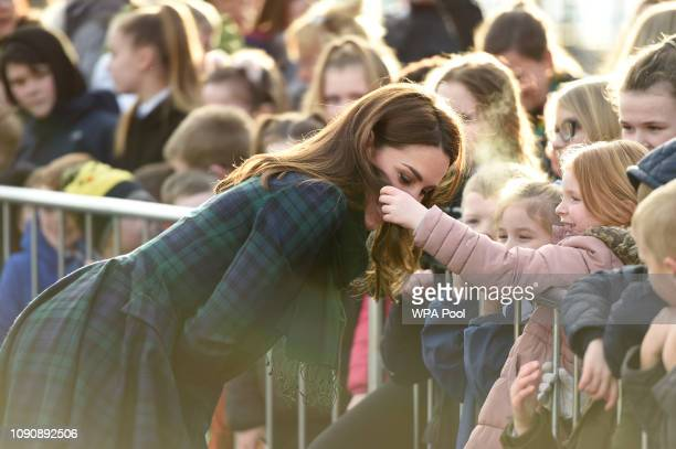 Catherine Duchess of Cambridge who is known as the Duchess of Strathearn in Scotland lets a girl touch her hair as she meets school children outside...