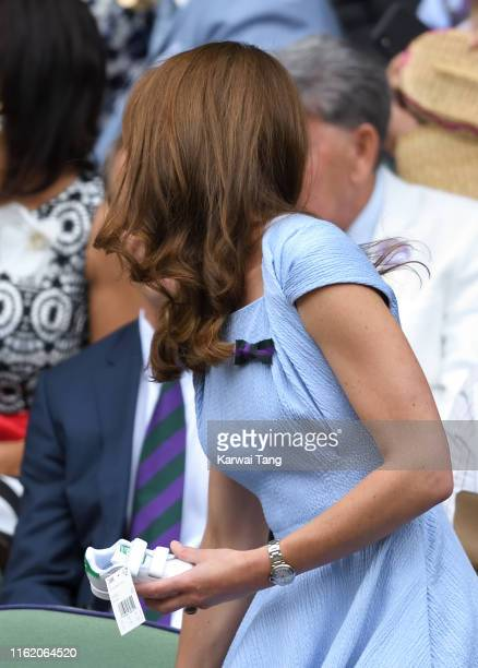 Catherine Duchess of Cambridge with a signed baby 'Stan Smith' trainer given to her by Stan Smith in the Royal Box during Men's Finals Day of the...