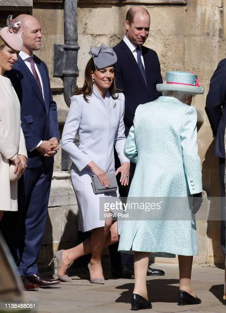 Catherine Duchess of Sussex curtsies as Queen Elizabeth II arrives for the Easter Sunday service at St George's Chapel on April 21 2019 in Windsor...