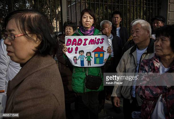 Catherine Gang whose husband is a missing passenger on Malaysia Airlines flight MH370 holds a sign as she and other relatives protest outside the...