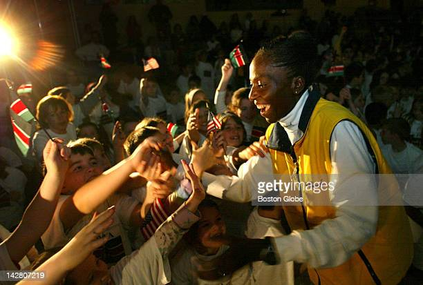 Catherine Ndereba of Kenya is greeted by the students of Elmwood Elementary School in Hopkinton during a visit there today with 12 other members of...