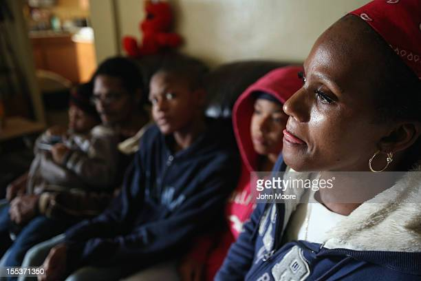 Catherine Orange sits with her family in their 13th floor apartment in the Red Hook public housing project on November 3 2012 in the Brooklyn borough...