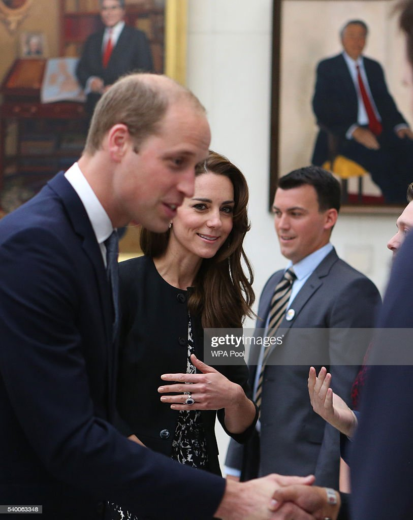 Catherine, The Duchess of Cambridge looks on as Prince WIlliam, The Duke of Cambridge meets staff after signing a book of condolence for Orlando mass shooting victims at the US Embassy on June 14, 2016 in London, England.